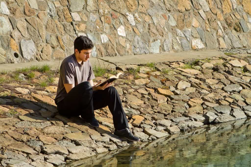 Man Reading Book of Mormon By Lake